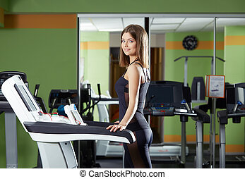 Attractive girl exercising on treadmill in gym