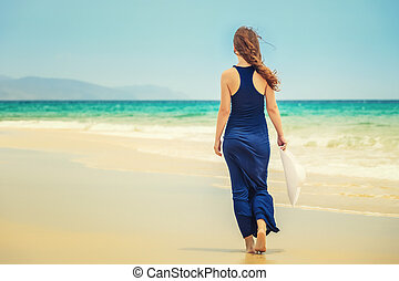 Young woman on ocean beach - Young woman walking on ocean...