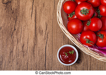 bowl of tomato sauce ketchup and tomatoes on wooden table...