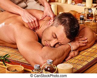 man getting bamboo massage - Big man with eyes closed...