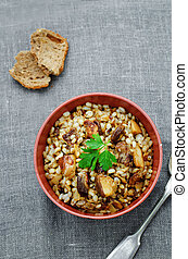 barley porridge with mushrooms on a dark background....