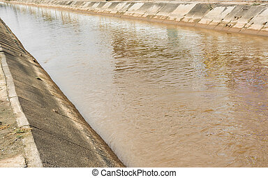 brown cement river - image of brown water with cement canal...