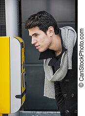 Man bending down peering inside a door - Handsome stylish...