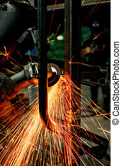 industrial working of grinding sparks with worker