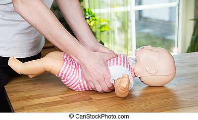 Baby CPR two hand compression - Woman performing CPR on baby...