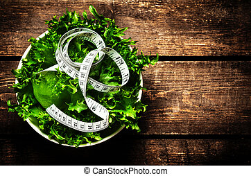 Salad and measuring tape on rustic wooden background. Diet...