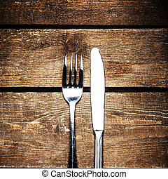 Knife and fork over wooden table with copy space. Diet Food...