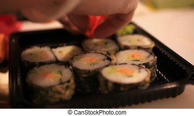 Close up of sushi chef puts in a container for sale In...