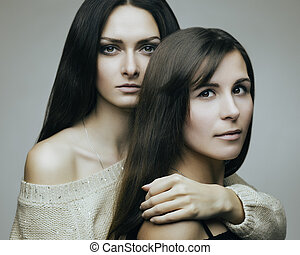 Friends - Artistic portrait of young brunette women on gray