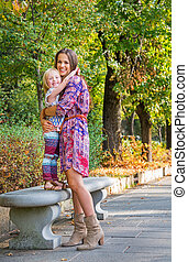 Happy mother and baby girl hugging in city park