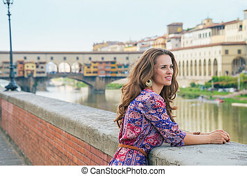 Thoughtful young woman on embankment near ponte vecchio in...