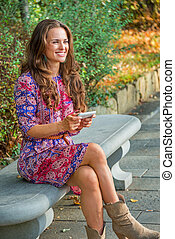 Happy young woman writing sms while sitting on bench in city...