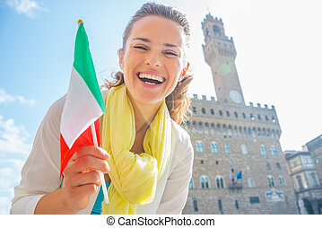 Happy young woman with flag in front of palazzo vecchio in...