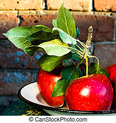 Red Big Apples with green leaves on rustic vintage...