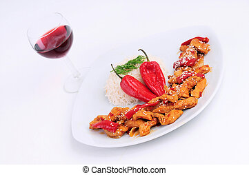 A glass of wine with a plate rice and  special chicken
