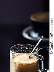 Cup of Cappuccino Coffee in Cafe on dark table close up....