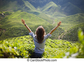 freedom girl with hands up in mountains