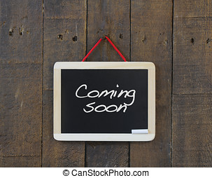 Coming soon. - Blackboard hanging on a old wooden wall with...