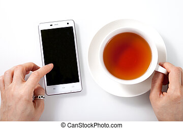 White smartphone and a cup of tea on white glass table and woman