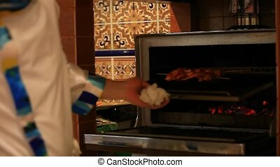chef puts meat skewers in the oven Camera shift motion HD...