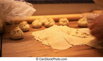 male chef hands preparing dough with rolling pin for asian...