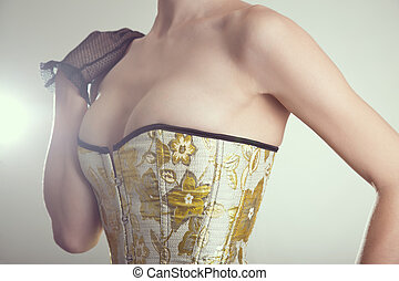 Close-up shot of sexy young woman in corset with golden embroide