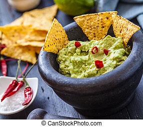 Mexican food - black stone bowl with fresh guacamole and...