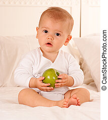 Baby and fruit - Cute baby on a bodysuit holding a green...