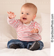 Babbling baby - Cute baby boy sitting on a bed happily...