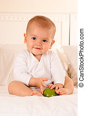 Happy baby with green apple