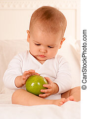 Baby inspecting green apple
