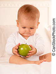 Baby beholding green apple - Cute baby on a bodysuit holding...