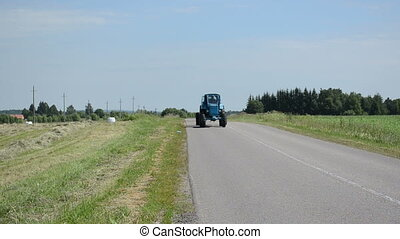 tractor field straw bale - Tractor drive on rural road and...
