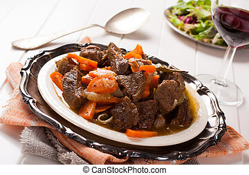 Stew with beef and carrots in a plate, horizontal