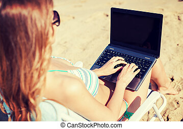 girl looking at laptop on the beach - summer holidays,...