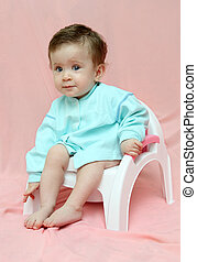pretty baby sitting on chamber-pot on pink background