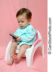 baby with pocket PC on chamber-pot - baby with pocket PC...