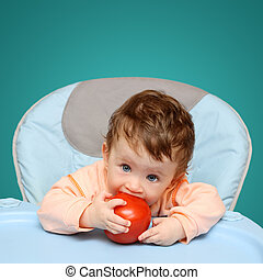 small baby biting tomato - small baby sitting on chair...