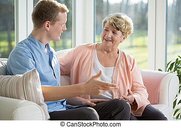 Male nurse and senior woman sitting on the couch