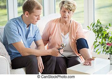 Nurse taking blood pressure - Man working as a nurse taking...