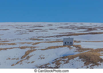 Small hut on snow hill