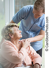 Male nurse caring about ill woman - Male nurse caring about...