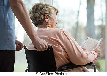 Disabled woman in retirement home - Disabled woman reading...