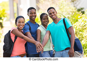 group of african college students putting hands together