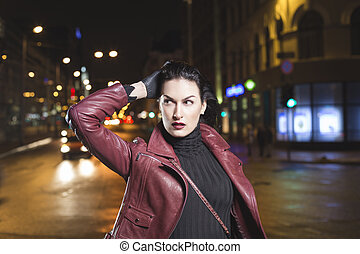 Woman is going out shopping in a night city