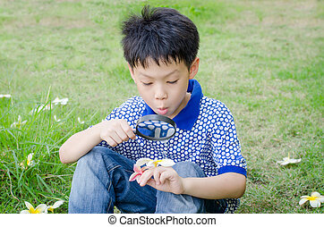 Asian boy exploring the environment with a magnifying glass