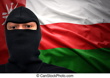 omani danger - dangerous man in a mask on a omani flag...