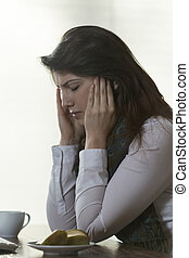 Young woman having headache sitting at the desk