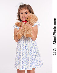 Girl hugging teddy bear - Little girl lovingly holding a...
