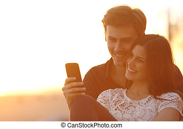Back light of a couple sharing a smart phone - Back light of...